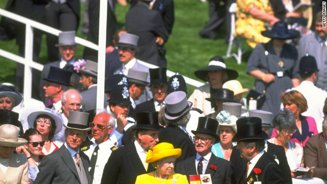 Her Majesty pictured with race goers during the Ever Ready Derby at Epsom racecourse in Epsom, England. It is said in racing circles that the British sovereign's reading material of choice over her breakfast is the Racing Post.