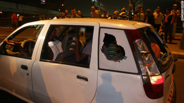 African immigrants drive a car with windows shattered by Israeli protesters in Tel Aviv Wednesday.