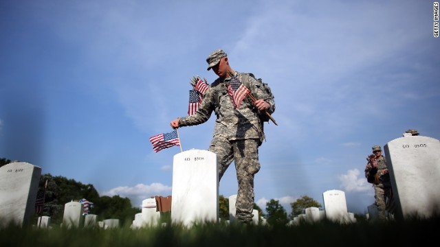 Members of the 3rd U.S. Infantry Regiment place flags at the graves of U.S. soldiers buried at Arlington National Cemetery.