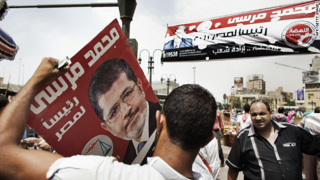 A supporter of the Muslim Brotherhood's presidential candidate holds a campaign poster in Cairo Friday. 