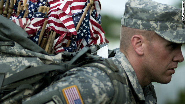 A soldier carries flags at Arlington National Cemetery on Thursday.