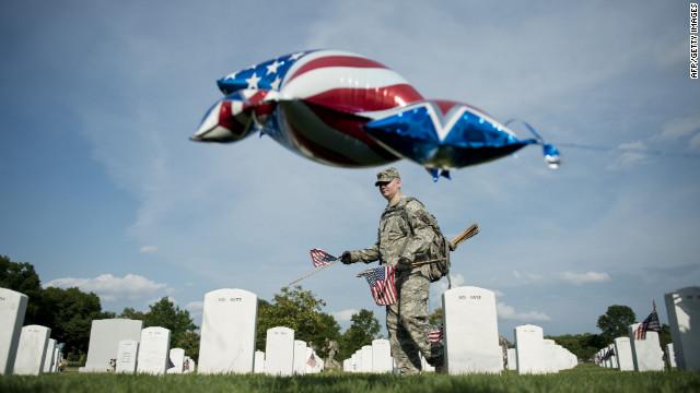 A soldier plants a flag at Arlington National Cemetery on Thursday.