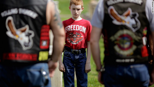 Martin Given, 12, of Springfield, New Jersey, stands with U.S. veterans including his father, Mark Given, who served in the Army for eight years, during a wreath-laying ceremony Friday at the Congressional Cemetery in Washington.