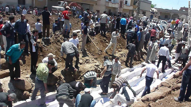 People gather at a mass burial for victims in Houla in this handout image dated May 26.
