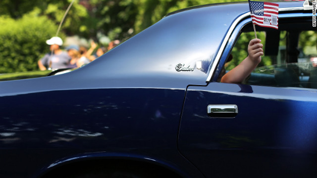 A boy waves an American flag from the window of a car participating in a Memorial Day parade in Fairfield, Connecticut, on Monday, May 28.