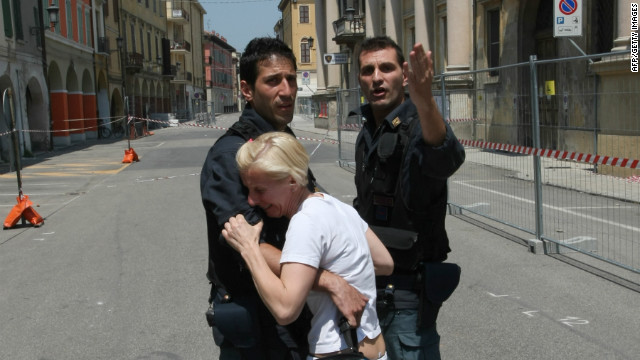 A distraught woman is comforted by policemen after the earthquake, which has killed at least 17 people.