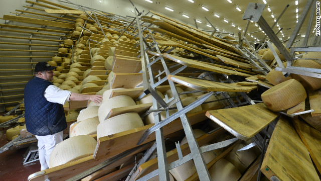 Hundreds of blocks of cheese fell on top of one another at a parmigiano factory in San Giovanni, Parsiceto. The owner of the factory surveys the damage on May 21, 2012, following an earlier quake.