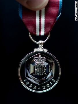 A British soldier holds a medal specially created for the diamond jubilee celebrations. Soldiers from the Household Cavalry Mounted Regiment will escort the queen during her procession on June 5.