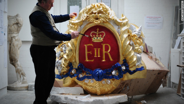 Head of Historic Carving Alan Lamb, poses next to the royal cypher that will decorate the Royal Barge in which the queen will travel along the Thames during the river pageant on June 3. 