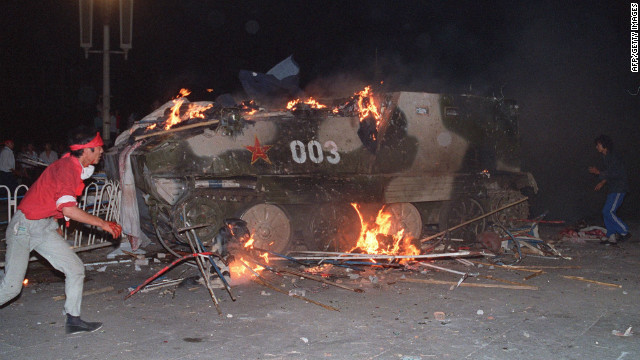 An armored personnel carrier is set on fire by students.