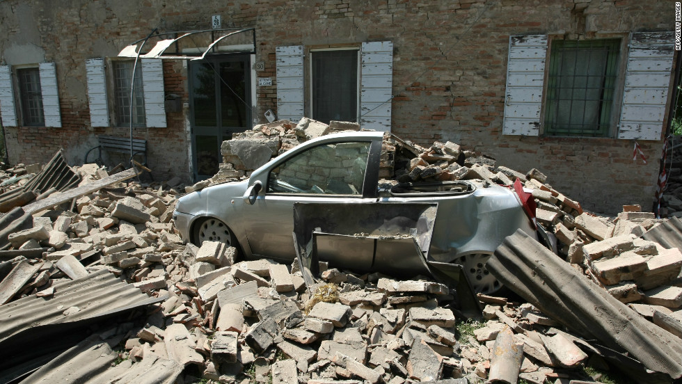 A car is crushed by falling rubble from a building in Carvezzo, Italy following the 5.8-magnitude earthquake on May 29, 2012.