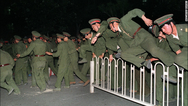 People's Liberation Army soldiers leap over a barrier in Tiananmen Square.