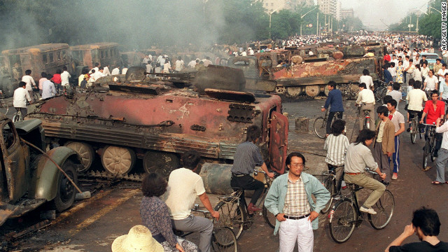 Residents pass by armored personnel carriers burnt by demonstrators to prevent troops from moving into Tiananmen Square.