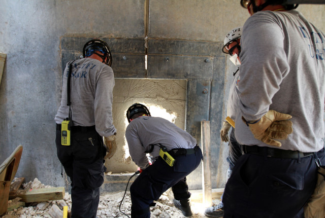 Search-and-rescue personnel break through concrete -- a painstaking task.