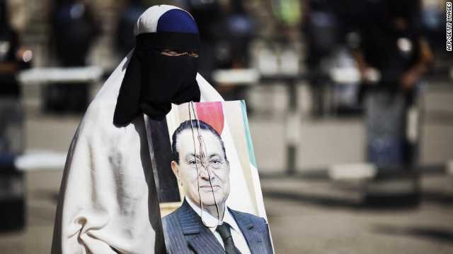 A woman holds a portrait of Mubarak outside the courthouse in Cairo. The image is adorned with a hangman's noose.