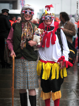 Two pageant spectators dressed as the queen (complete with corgi) and a