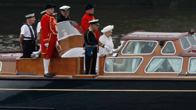 The queen and the Duke of Edinburgh make their way to the royal barge, The Gloriana, which is crewed by 18 oarsmen and is leading the flotilla down the Thames.