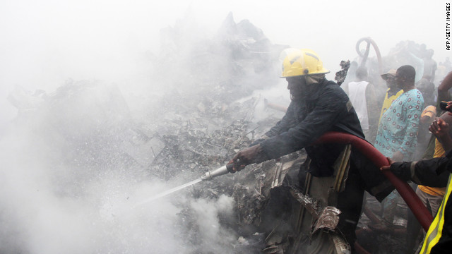Firefighters work at the scene of the crash. The Dana Air flight from Abuja plunged into a building several miles from the airport in Lagos.