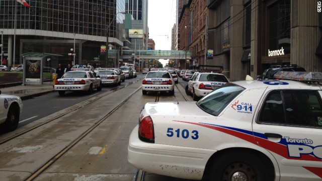 Police, firefighters and paramedics gather outside Toronto's Eaton Centre shopping mall after reports emerged of a shooting at the food court.