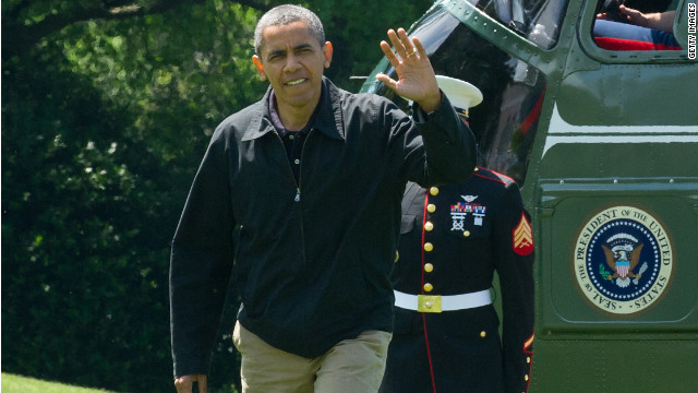 Barack Obama waves as he arrives at the White House on Sunday after spending a day at the Camp David retreat.