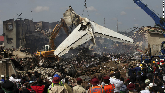 The scene is surrounded by onlookers as pieces of the wreckage and debris are cleared Monday.