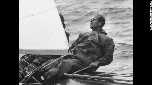 "August 1962: Prince Philip at the helm of his yawl, ""Bloodhound,"" during Cowes Regatta."