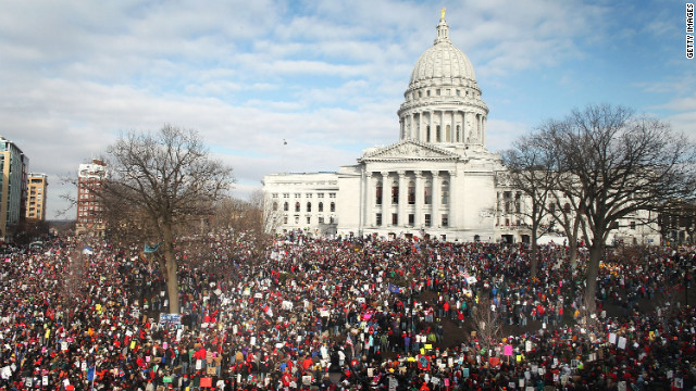 Thousands of demonstrators gather outside the Wisconsin State Capitol in Madison the following day to protest the bill signing.