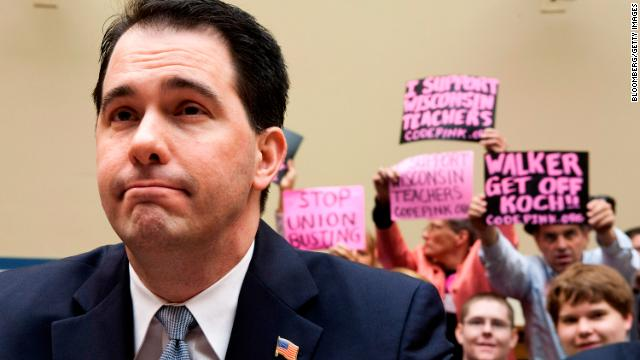 Walker testifies at a House Oversight and Government Reform Committee hearing on Capitol Hill in Washington as protesters wave signs behind him, April 14, 2011.