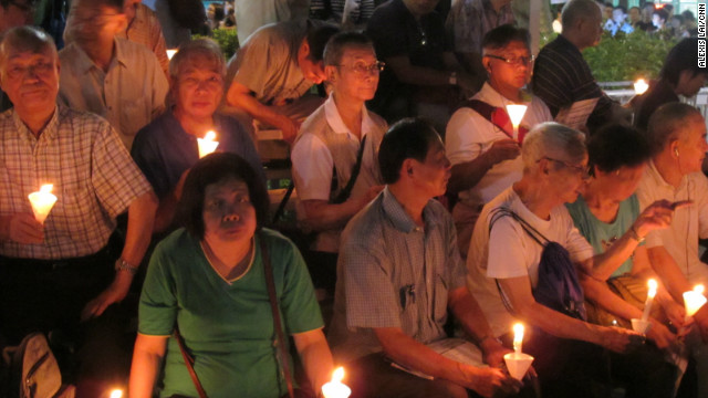 "Sitting on bleachers with a group of elderly men holding lit candles in paper cones, 73-year-old Fu Kam-tin says he has been coming to the vigils nearly every year since 1989. Fu, who emigrated from the mainland at age 12, calls the Tiananmen crackdown ""the most apparent example in China's history of the strong bullying the weak."" He says he continues to be ""very angry and unsettled by these corrupt officials who are harming our country and harming the world."""