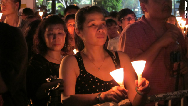 Mourners hold candles placed in paper cones in an outpouring of compassion, a continued sense of injustice, and fear for the future.
