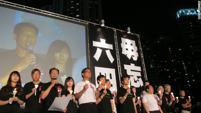 "Representatives from the Hong Kong Alliance in Support of Patriotic Democratic Movements of China and Hong Kong Federation of Students take to the stage against a backdrop imploring ""Don't forget June 4."""