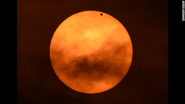 Venus appears as a black spot against the sun on Tuesday, as seen from the west side of Manhattan in New York. Astronomers around the world are training their telescopes on the skies to watch the transit of Venus as it passes between Earth and the sun.