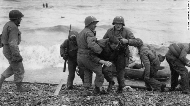American troops help their injured comrades after their landing craft was fired upon. Allied forces secured the beaches at a cost of about 10,000 casualties.
