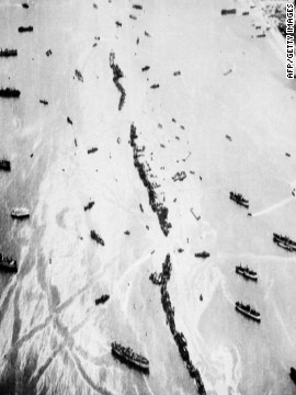 An aerial view shows 32 intentionally-sunk American merchant ships, known as Liberty Ships, which served as both a breakwater and offshore anti-aircraft platforms during the invasion.