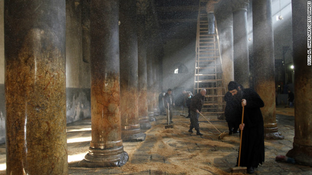 Orthodox clergy cleaning the Church of Nativity. Responsibilities for cleaning the church are split between the three denominations that administer the church, and have been known to erupt in scuffles.