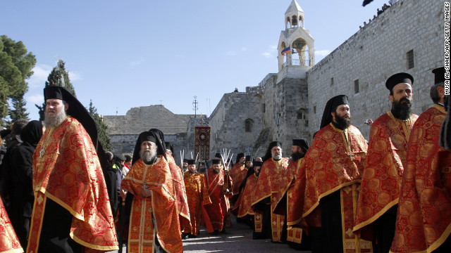 Orthodox priests take part in a procession in Bethlehem's Manger Square, outside the Church of the Nativity.