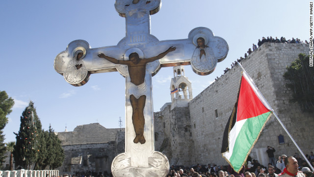 A cross held aloft in Manger Square, next to a Palestinian flag. One of Christianity's holiest sites, the Church of the Nativity is one of the biggest tourist destinations in the Palestinian Territories, and drew about 2 million visitors last year.