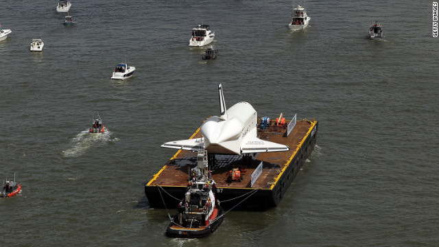 Boats surround the Enterprise as it makes its way up the Hudson River. The shuttle was flown into JFK on the back of a 747 on April 27.