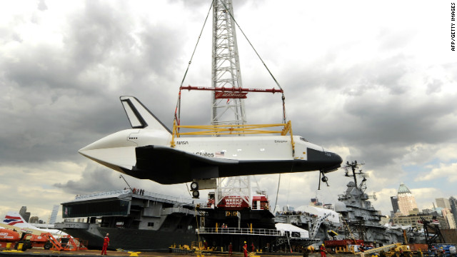 A giant crane carefully swings the Enterprise from the barge that transported it down the Hudson River toward the Intrepid.
