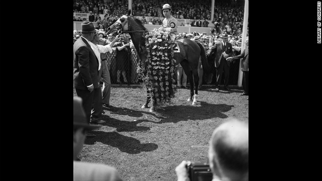 Count Fleet, who won the Triple Crown in 1943, is adorned with a garland of flowers after winning the Preakness Stakes in 1943.