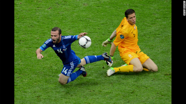 Wojciech Szczesny of Poland fouls Dimitris Salpigidis of Greece for a penalty.