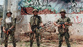 Syrian soldiers patrol in a southern suburb of Beirut 27 May 1988, in front of an Amal frescoes, after heavy inter-Shi'ite clashes erupted between pro-Syrian Amal movement and pro-Iranian Hezbollah militia.
