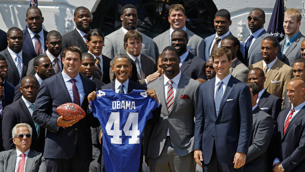 President Barack Obama with a personalized jersey presented to him by the Super Bowl champion New York Giants on June 8, 2012. From left: Zak DeOssie, Victor Cruz and Eli Manning