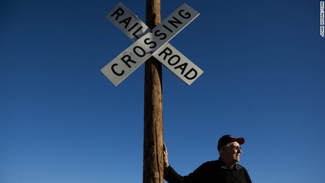 Historian Richard Dean stands next to a sign by the old railroad tracks. Dean runs the Columbus Historical Society and Old Railroad Depot Museum and has helped establish historical markers around the town, most of which feature the raid by Pancho Villa and his army in 1916. Dean's great-grandfather was shot and killed in the raid.
