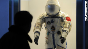 A visitor at the Shanghai Science & Technology Museum looks at a spacesuit used by Chinese astronauts.