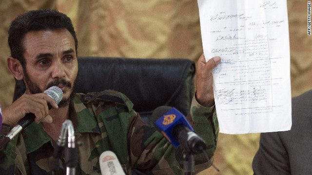 The commander of the Zintan brigade shows a document during a press conference Saturday.