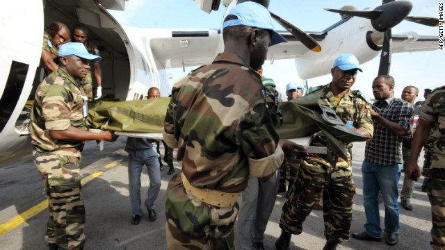UN troops carry on a stretcher the body of one of the seven UN peacekeepers from Niger who were killed in an ambush, at the airport in Abidjan on June 9, 2012.