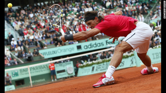 Nadal reaches and slides on the clay to return a ball from Djokovic.
