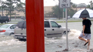 Cars attempt to navigate high water Sunday in Escambia County, Florida.