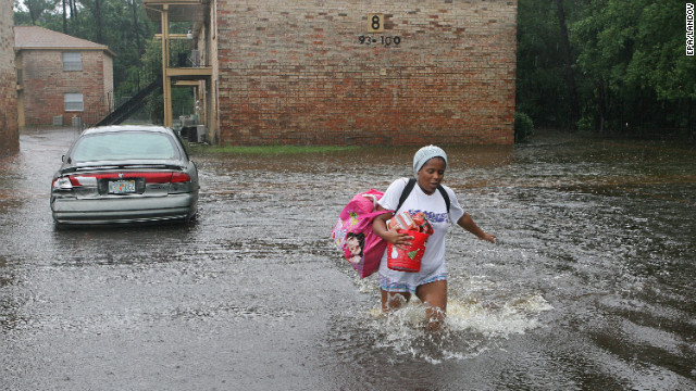 Scoobi Griffin splashes through the parking lot of her flooded Pensacola complex Sunday.